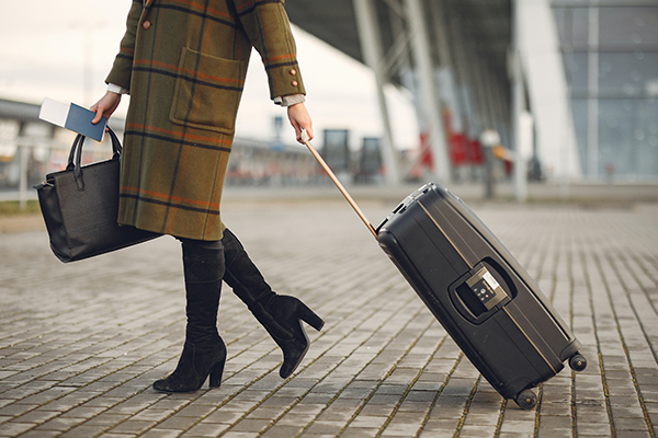 woman leaving an airport with her suitcase