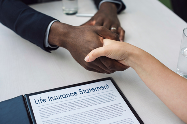 two people shaking hands over a life insurance statement